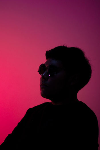 Portrait of young man looking away over pink background