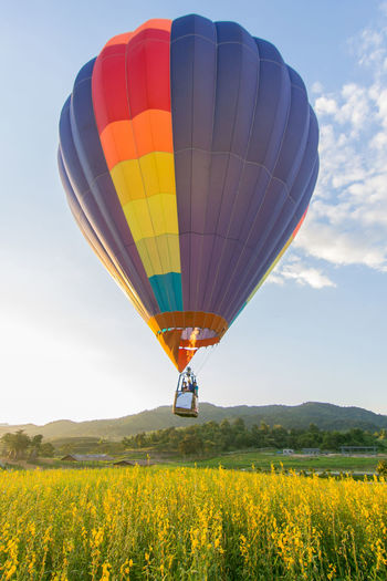 Yellow hot air balloon flying over field against sky