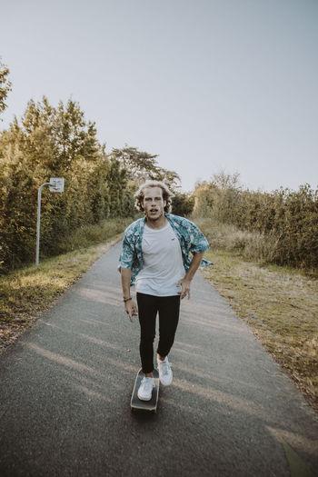 Full length portrait of smiling man on road