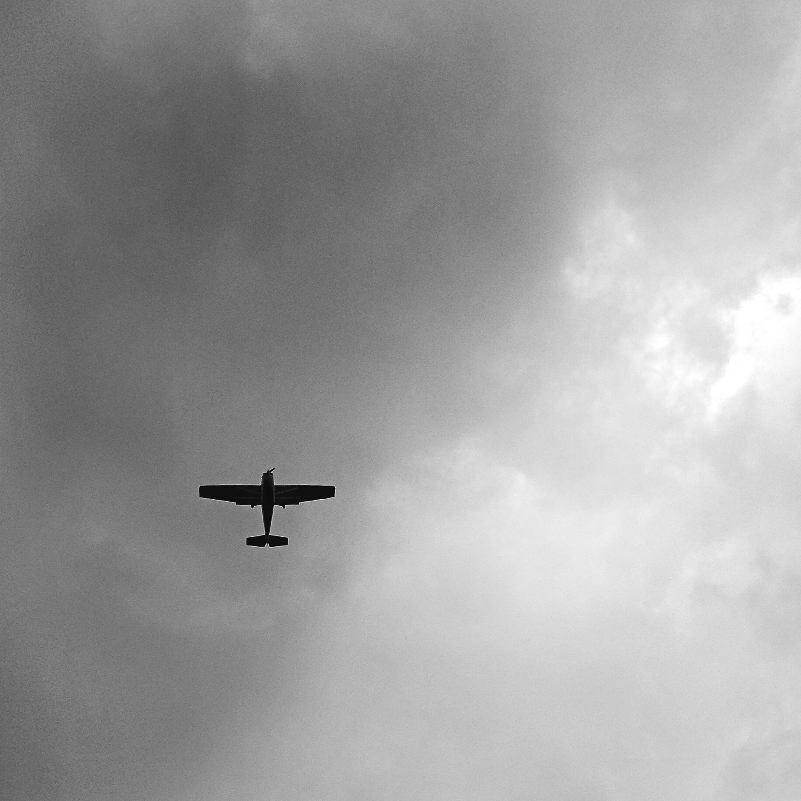 flying, airplane, air vehicle, low angle view, transportation, mode of transport, mid-air, sky, cloud - sky, on the move, travel, journey, commercial airplane, silhouette, public transportation, outdoors, copy space, helicopter, day, cloudy