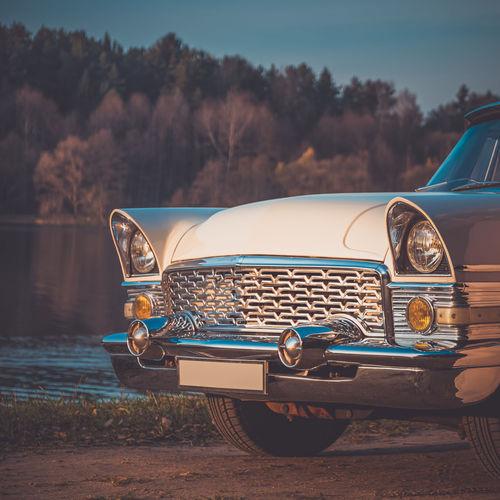 Vintage car on road by lake