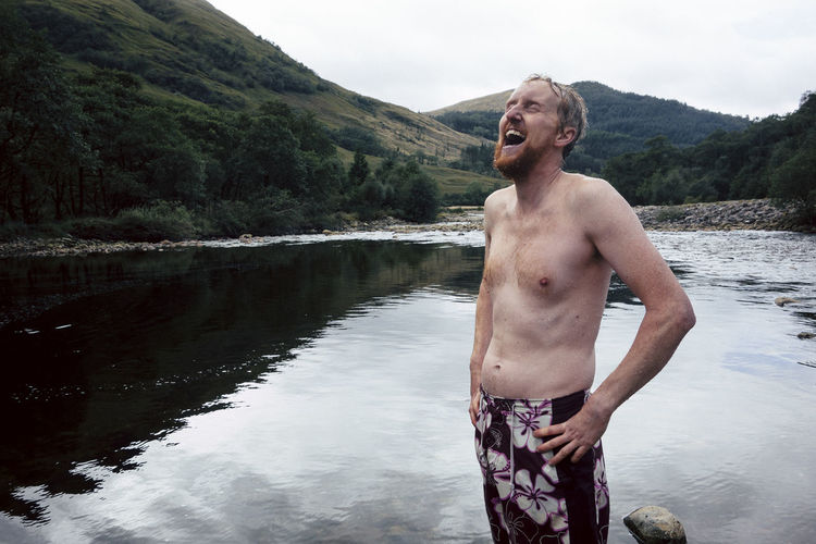 Shirtless laughing man standing at lake against sky