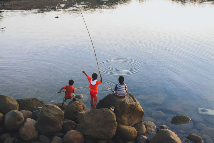 High angle view of people fishing in lake