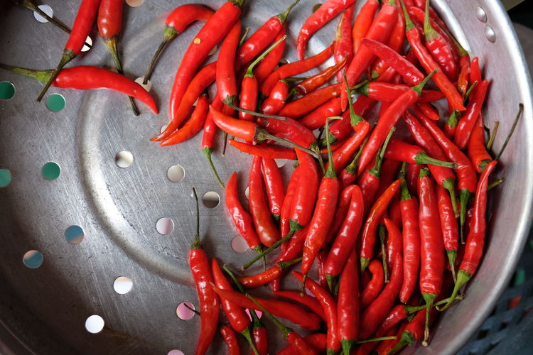 High angle view of red chili peppers in colander