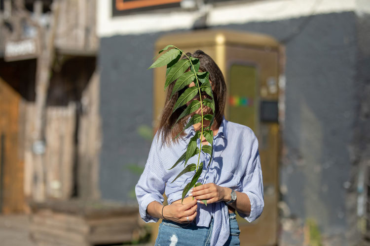 Young woman covering face with twig while standing outdoors