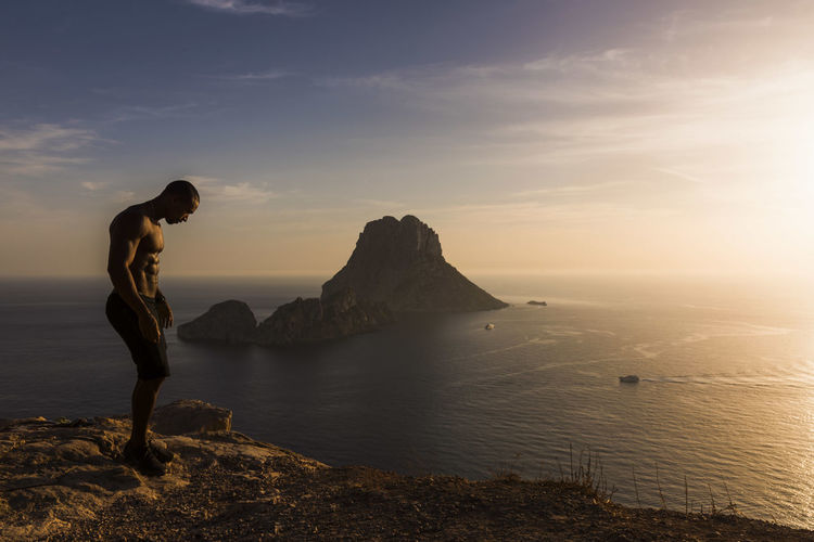 Side view of muscular man standing on rock by sea against sky during sunset