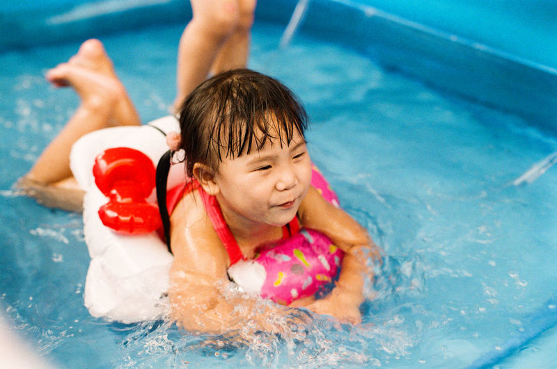 Asian little girl swimming in the pool. Pool Swimming Pool Child Childhood Water Males  Leisure Activity Swimming Real People Offspring Lifestyles Enjoyment Nature People High Angle View Outdoors Innocence Floating On Water Kids Girl Swimming Nature Fun One Person Innocence Innocence Swimming Fun