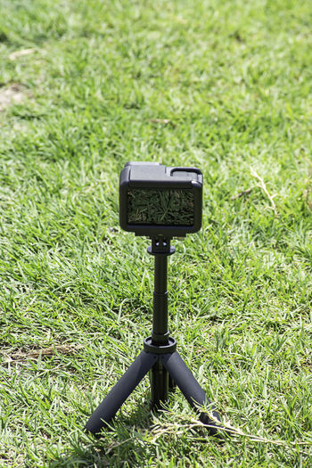 Camera and video with small black stand on On the green grass Symbol Post Garden Park Summer Sign Grass Nature Outdoor Green Background Black Camcorder Camera Compact Digital Equipment Fast Flexible Hold Image Legs Lens Media Mini Mobile Modern New Object Photo Photograph Photographer Photographic Photographing Photography Plastic Portable Professional Protection Screen Shot Small Stability Technology Telephoto Tool Tripod Tripods Vertical Video