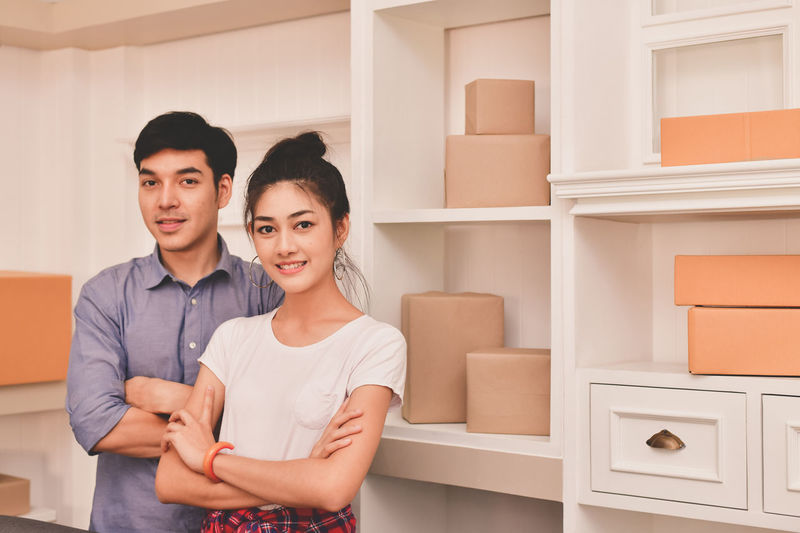Adult Box Box - Container Couple - Relationship Emotion Front View Indoors  Lifestyles Looking At Camera Men Portrait Positive Emotion Real People Smiling Standing Togetherness Two People Waist Up Women Young Adult Young Men Young Women