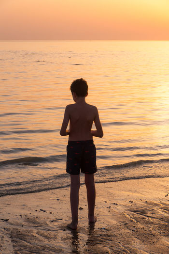 Rear view of shirtless boy standing at beach against sky during sunset