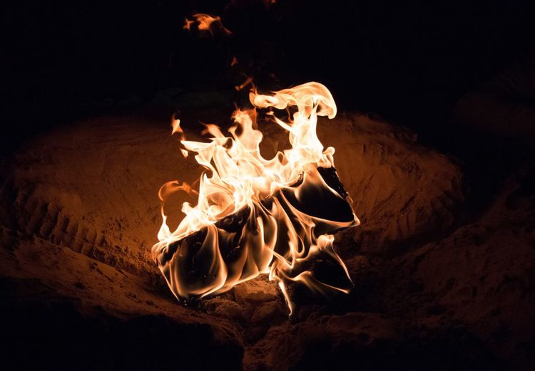 Close-Up Of Fire On Sand At Beach