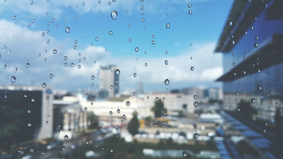 Water drops on glass against blurred buildings