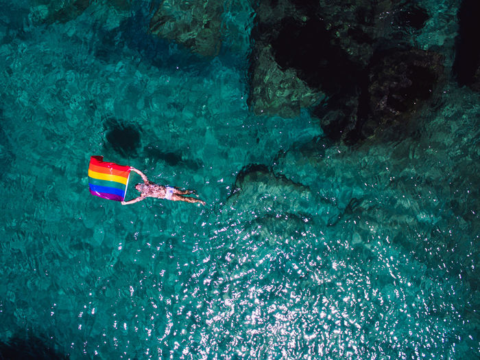 Aerial view of man swimming with rainbow flag