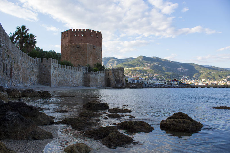 Alanya historic building by sea against sky