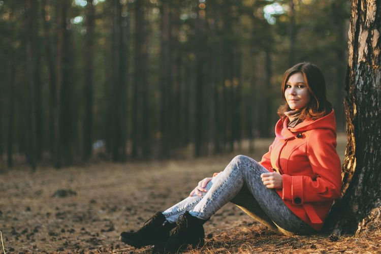 Portrait of young woman sitting against tree in forest
