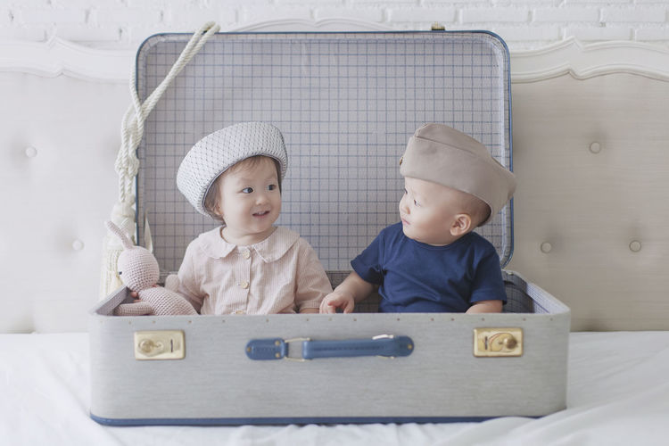 Cute girl and boy sitting in suitcase on bed at home