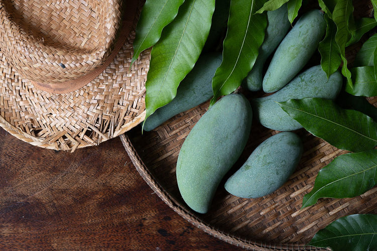 Green mango and mango leaves in a basket on a wooden table limited edition and seasonal only. Thai Agriculture ASIA Background Basket Color Delicious Dessert Diet Food Fresh Fruit Fruits Green Health Healthy Mango Mangoes Natural Nature Nutrition Organic Raw Tropical Vitamin White Wooden Yellow