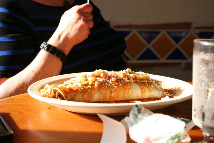 Midsection Of Man Having Burrito In Restaurant