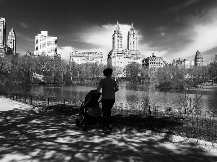 Woman With Baby Carriage Walking On Street By River