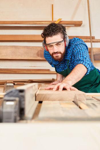 Man working on wood in workshop