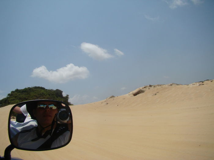 Reflection Of Man On Side-View Mirror On Vehicle At Desert Against Sky