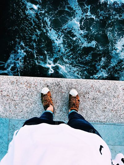 Low section of man wearing shoes while standing on retaining wall by river