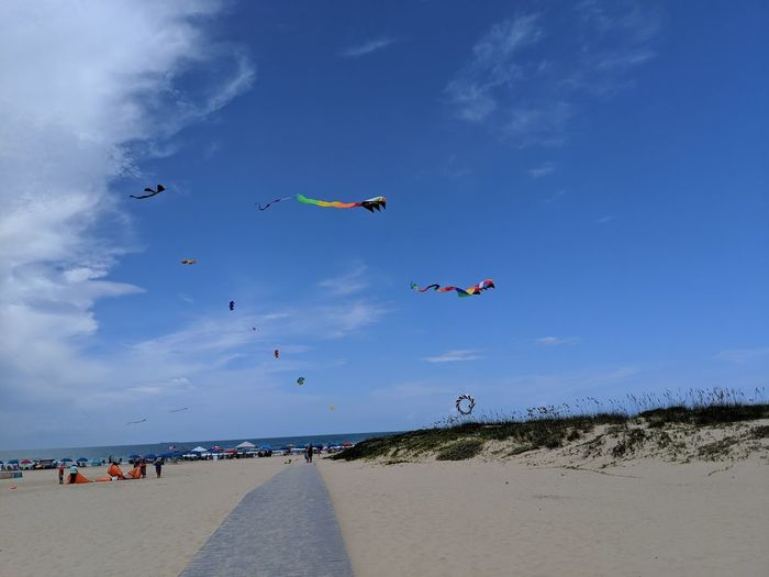 Scenic view of beach against blue sky with kites