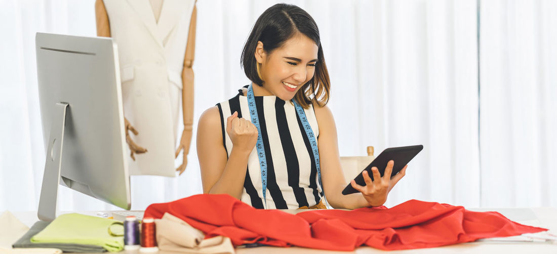 Cheerful woman looking at digital tablet in boutique