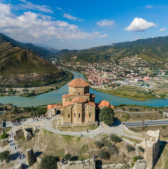 Jvari Jvari Monastery Mtskheta Aerial View Architecture Blue Sky Building Building Exterior Built Structure Cloud - Sky Day Environment High Angle View History Landscape Mountain Mountain Range Nature Outdoors Plant River Scenics - Nature Sky Travel Travel Destinations