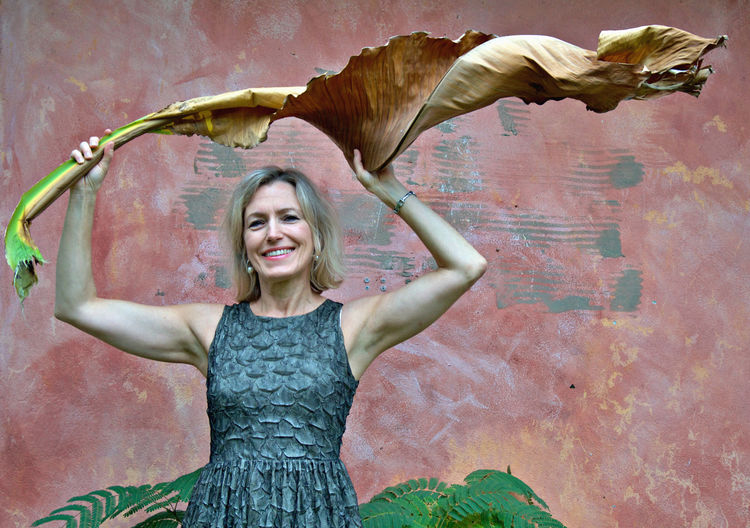 Portrait of smiling woman holding banana leaf standing against wall