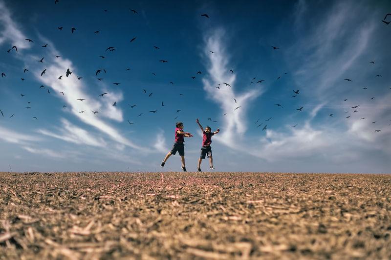 People flying kite on field against sky