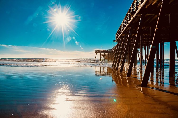 Water Sky Architecture Sea Reflection Nature Sunlight Built Structure Sun Lens Flare No People Beach Pier Beauty In Nature Tranquility Blue Scenics - Nature Sunbeam Tranquil Scene Outdoors Bright
