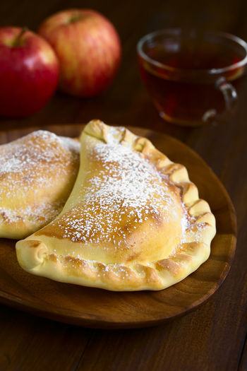 Chilean apple empanada with icing sugar, cup of tea in the back, photographed on dark wood with natural light (Selective Focus, Focus one third into the image) Apple Chile Chilean  Empanadas Filled Latin American Food  South American Food Stuffed Apple Empanada Baked Breakfast Chilean Food Dessert Empanada Food Food And Drink Fruit Icing Sugar Latin American Pastry Snack South American Sweet Sweet Food Vertical