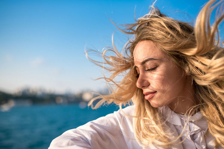 Close-up of beautiful woman with tousled hair against clear blue sky