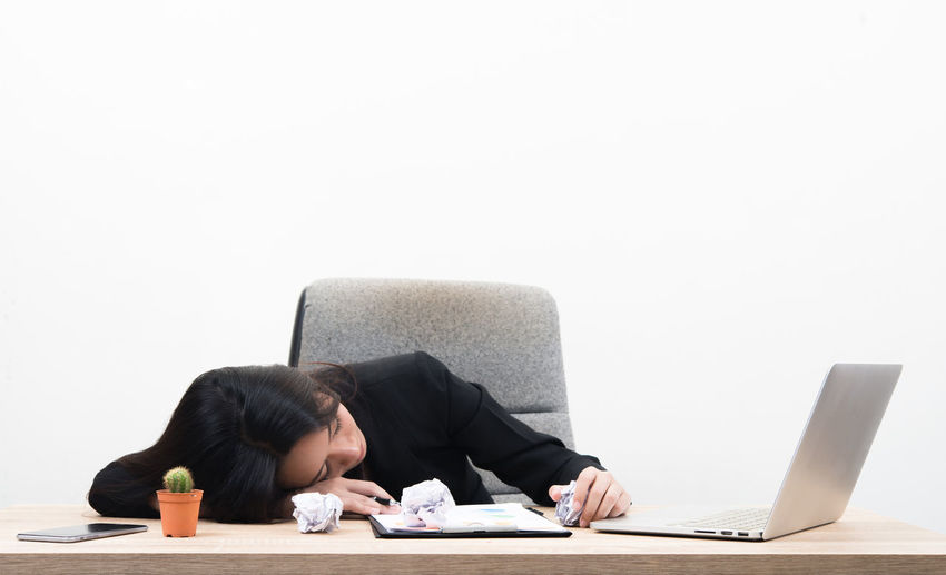Young Businesswoman Napping By Laptop On Table