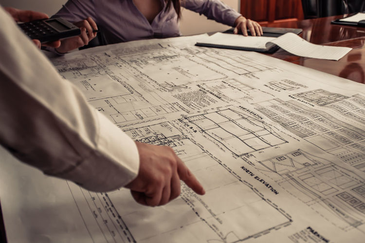 Cropped Engineer Pointing Finger On Blueprint