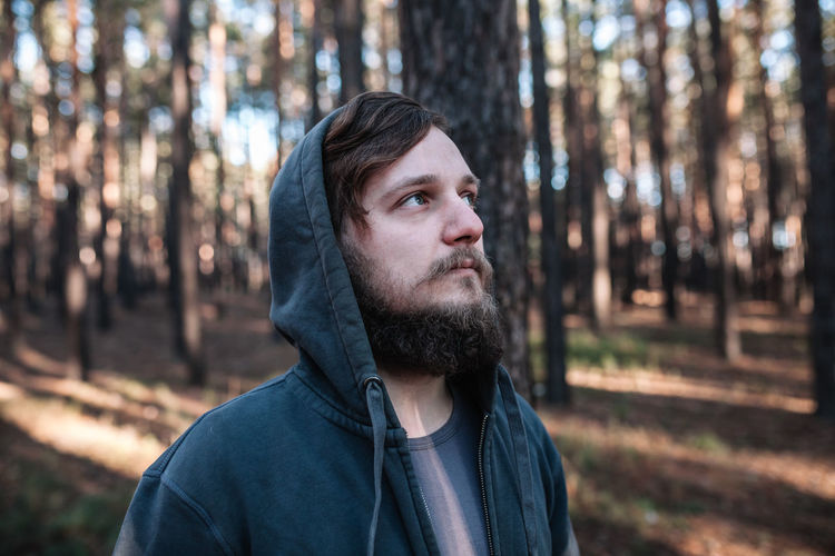 Thoughtful man wearing hooded jacket in forest