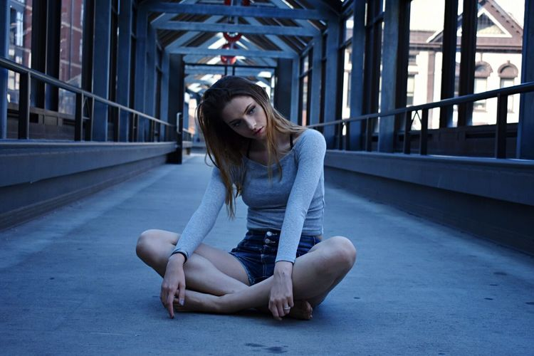Thoughtful young woman looking away while sitting on bridge