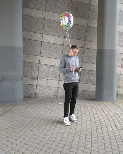 Man with balloon using mobile phone on footpath