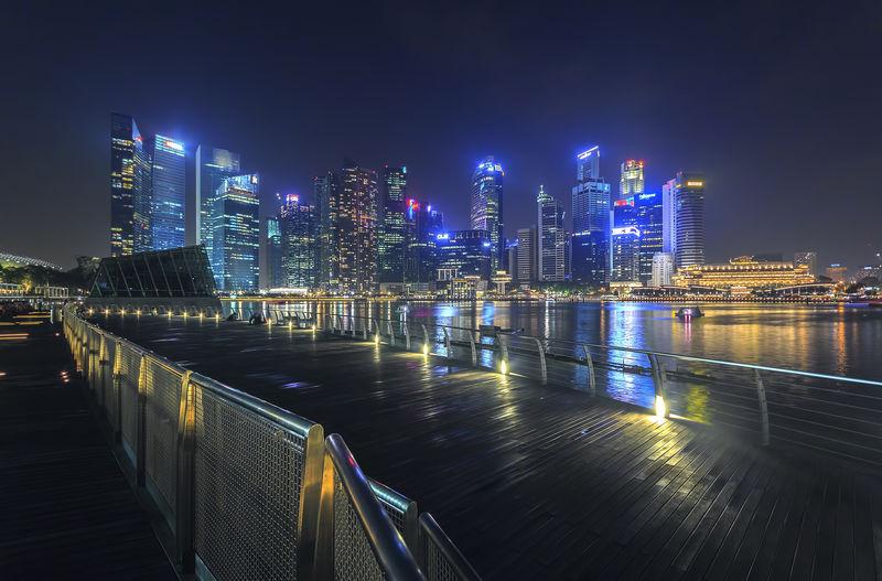 Marina bay sands boardwalk with illuminated city skyline at night
