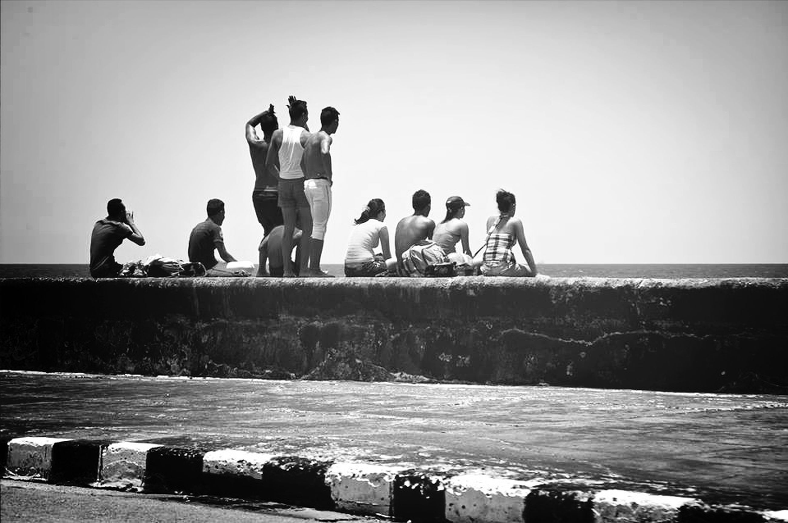 men, water, clear sky, togetherness, copy space, lifestyles, person, leisure activity, sea, friendship, medium group of people, standing, large group of people, bonding, pier, railing