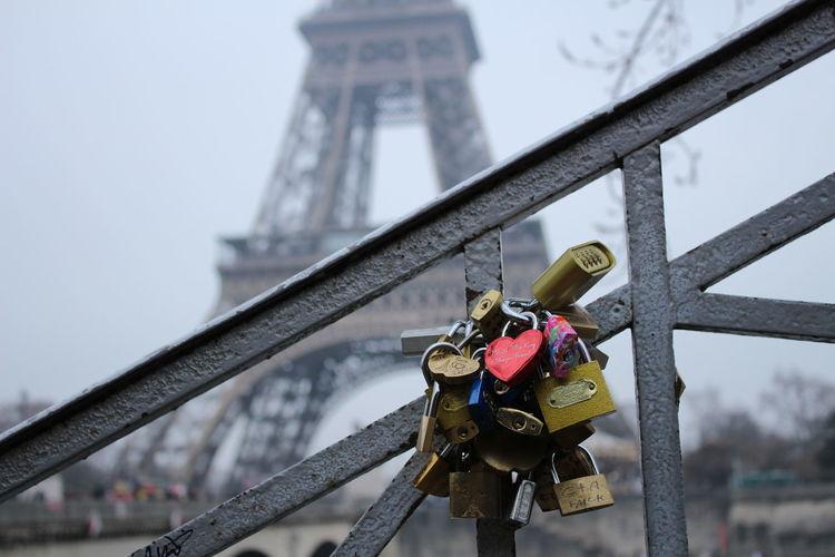 Close-Up Of Love Locks On Railing Against Eiffel Tower