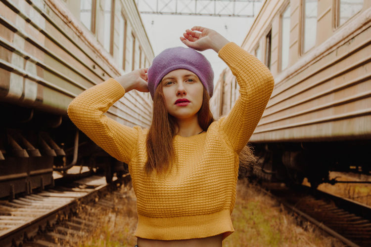 Portrait of fashionable young woman standing amidst train
