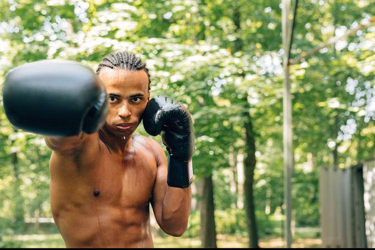 Portrait of shirtless man boxing on street