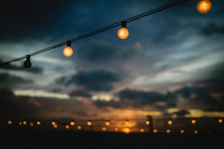 Aruba Beauty In Nature Blurry Bokeh Bulb Cable Cloud - Sky Dusk Electricity  Focus On Foreground Hanging Illuminated Light Light Bulb Lighting Equipment Low Angle View Nature No People Orange Color Outdoors Silhouette Sky Street Light Sunset Sunsets