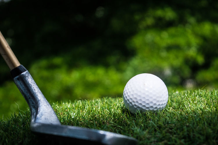 Close-up of golf stick and ball on field