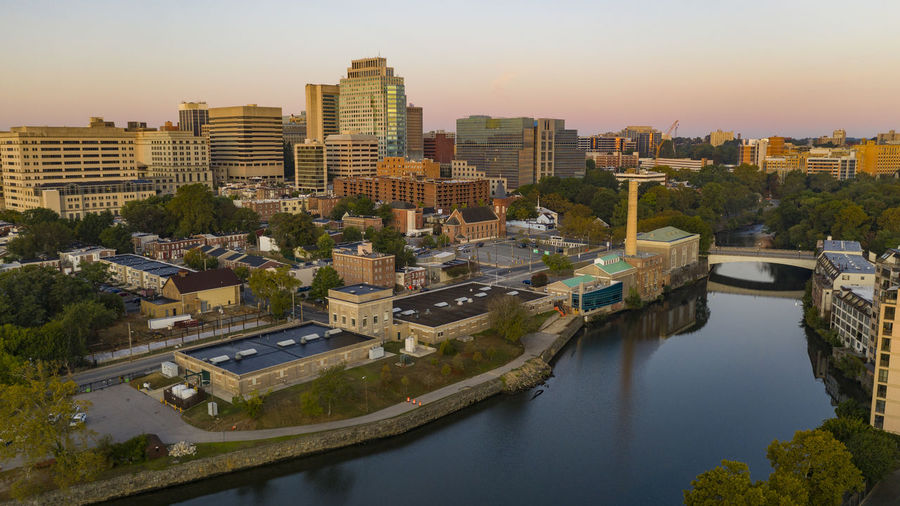 High angle view of river and buildings against sky at sunset