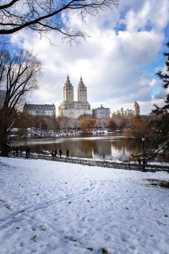 Central Park winter with skyscrapers and Bow Bridge in midtown Manhattan New York City Central Park Architecture Building Exterior Cold Temperature Nature Outdoors Sky Snow Travel Destinations Water Winter