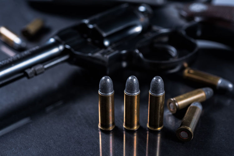 Close-Up Of Bullets And Handgun On Table
