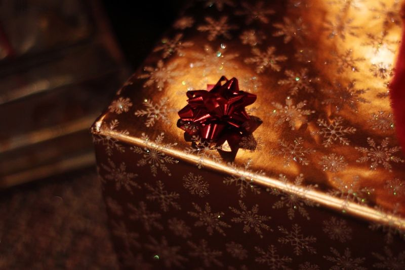 Christmas present wrapped in golden snowflake paper with a red bow Season  Holiday Gift Wrapping Paper Snowflake Present No People Close-up Indoors  Red Christmas High Angle View Celebration Focus On Foreground